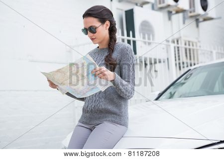 Woman wearing sunglasses reading map beside her car in a car park