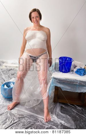 Pregnant young woman smiling during the making of her plaster belly cast