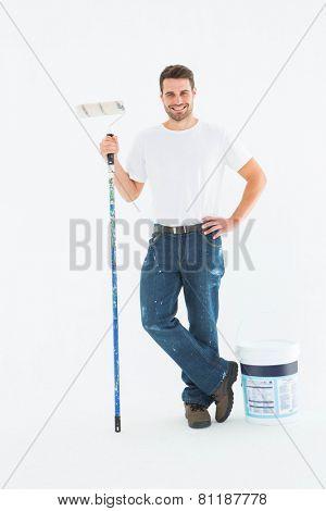 Full length portrait of happy man holding paint roller on white background