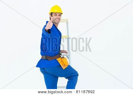 Portrait of repairman gesturing thumbs up while climbing step ladder over white background