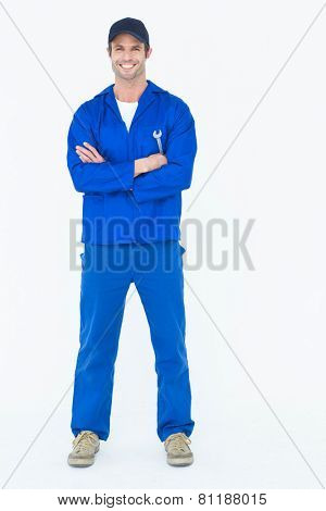 Full length portrait of confident mechanic holding wheel wrenches over white background