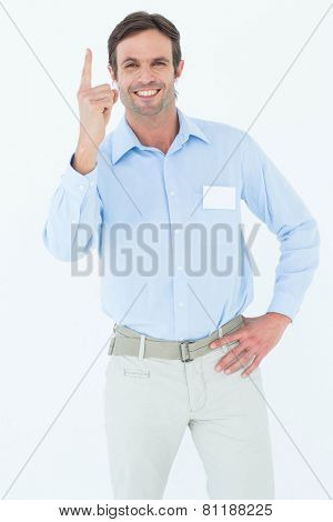 Portrait of confident businessman pointing upwards over white background