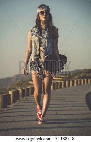 Beautiful skate girl walking while holding a skateboard