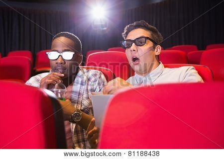 Astonished young friends watching 3d film at the cinema