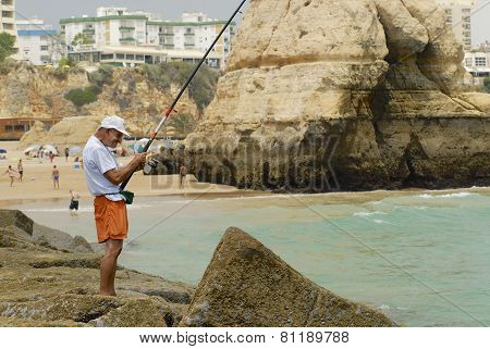Man does fishing at Praia da Rocha beach in Portimao, Portugal.