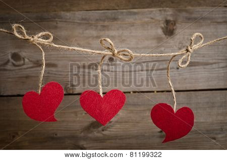 Three Red Fabric Hearts Hanging On The Clothesline . On Old Wood Background.