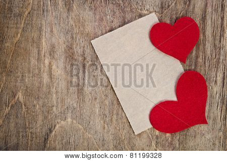 Two Red Fabric Hearts With Sheet Of Paper Lying On Old Wooden Background.