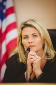 stock photo of court room  - Portrait of a serious judge with american flag behind her in the court room - JPG