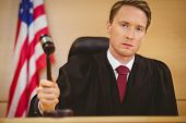 picture of court room  - Serious judge about to bang gavel on sounding block in the court room - JPG