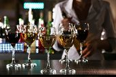 stock photo of bartender  - Bartender working at counter on bar background - JPG