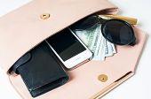 pic of clutch  - Cosmetics sunglasses money purse and smartphone in an open beige woman - JPG