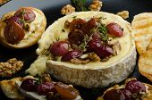 stock photo of brie cheese  - Brie cheese baked with nuts and grapes tasty and crispy baguette and bio herbs reduction of sugar nuts and balsamic vinegar - JPG