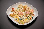 picture of christmas cookie  - white plate with colorful decorated christmas cookies on black table - JPG