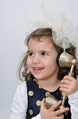 stock photo of babbler  - Cute young girl wearing a blue dress with gold spots and alice band with a white bow talking on the retro telephone - JPG
