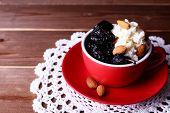 pic of doilies  - Dessert with prunes and almonds in red cup on lace doily and wooden planks background - JPG
