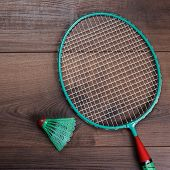 stock photo of shuttlecock  - shuttlecock and badminton racket on wooden table after the game - JPG