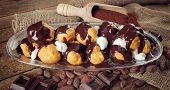 stock photo of chocolate spoon  - Chocolate profitteroles with cream cocoa powder cocoa beans and pieces of chocolate - JPG