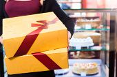 pic of takeaway  - Woman presenting cake and pastries in takeaway boxes in cafe or pastry shop - JPG