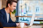 stock photo of adults only  - Side view of handsome young man working on laptop and smiling while enjoying coffee in cafe - JPG