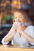 foto of toothless smile  - Through a glass shot of beautiful young woman keeping eyes closed and smiling while enjoying coffee in cafe - JPG