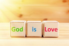 stock photo of godly  - God is Love text spelled in cubes on wooden background - JPG