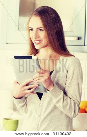 Young beautiful woman using a tablet computer at home