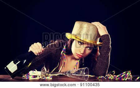 Young drunk woman sitting by a desk with empty champagne bottle after celebrating new years eve. On black background.