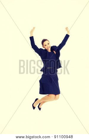 Happy excited businesswoman jumping with hands up