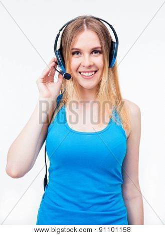 Happy female assistant operator in headset standing over gray background and looking at camera