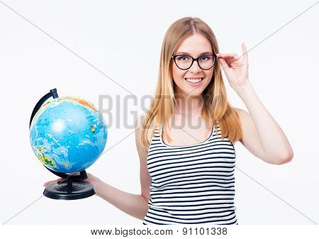 Happy girl in glasses holding world globe over gray background. Looking at camera