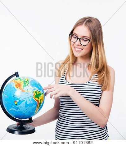 Young smiling woman in glasses holding world globe over gray background