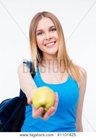 Smiling female student holding green apple over gray background and looking at camera