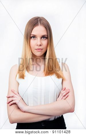 Serious young businesswoman standing with arms folded over gray background and looking at camera