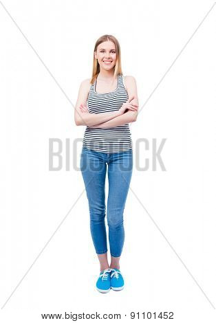Full length portrait of a smiling young woman standing with arms folded over white background and looking at camera