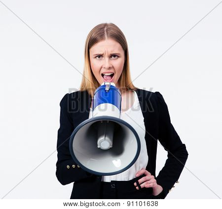 Young businesswoman shouting in megaphone at camera. Isolated on a gray background