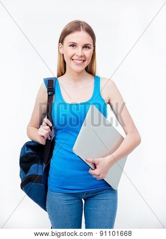 Portrait of a happy female student holding laptop and backpack over gray background. Looking at camera