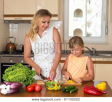 Stock Photo: Young woman and girl making fresh vegetable salad. Healthy domestic food concept. Moth