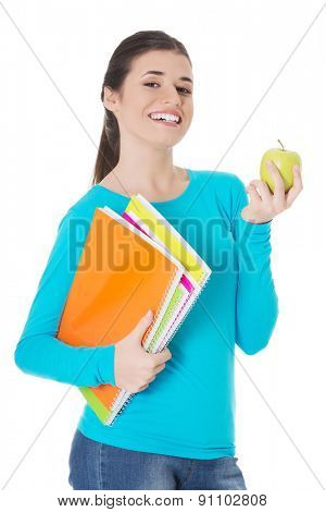 Happy woman holding an apple and notebooks.