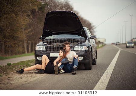 couple near a broken car on the roadside