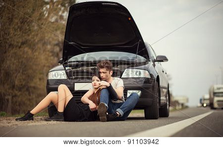 couple near a broken car on the roadside