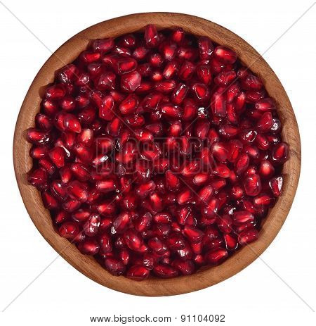 Pomegranate Seeds In A Wooden Bowl On A White