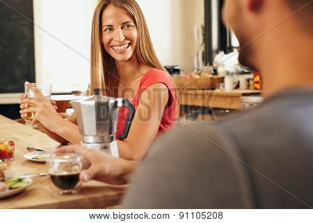 Happy Young Couple In The Kitchen Having Breakfast