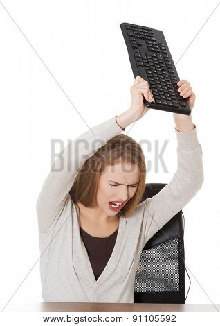 Angry woman throwing a pc keyboard.