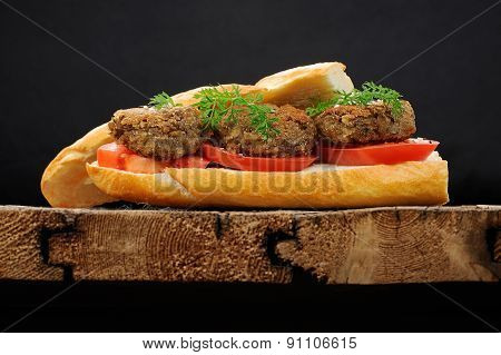 Lentil Patty Sandwich With Tomato And Carrot Greens In Old Wooden Board