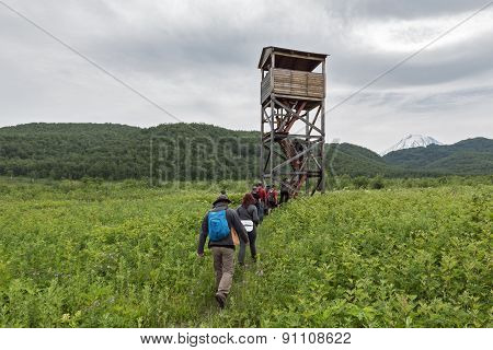 Group Of Tourists Go To Observation Tower. Nature Park Nalychevo, Kamchatka Peninsula