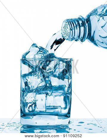 Water pouring from bottle to glass isolated