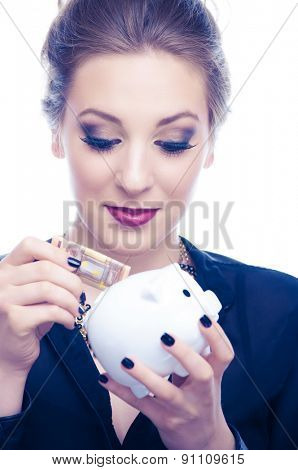 Young woman put 50 Euro banknote in a piggybank