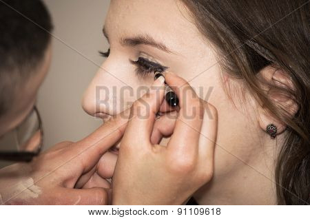 Beautician applying makeup on a model