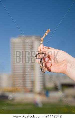 Child Hand Holding An Old Keys To The House Against The Sky