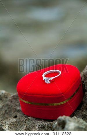 Wedding ring with heart shape symbol on beach rock